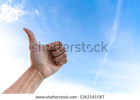 Man's hand showing thumb up on sky and cloud.Symbol that good job and cheering business people concept.free space.