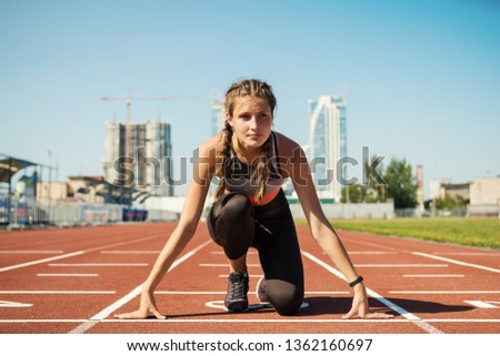 Concentrated female teen athlete in sportswear with fitness tracker on her wrist preparing for run on track at stadium #1362160697