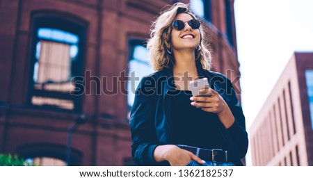 Happy millennial hipster girl in sunglasses laughing on urban setting during sunny day, positive cheerful woman tourist dressed in casual look holding smartphone gadget in hand for communicate #1362182537