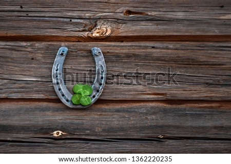 Old horseshoe and four leaf clover on a vintage wooden board. The concept of luck, luck, luck. St. Patricks Day card. #1362220235