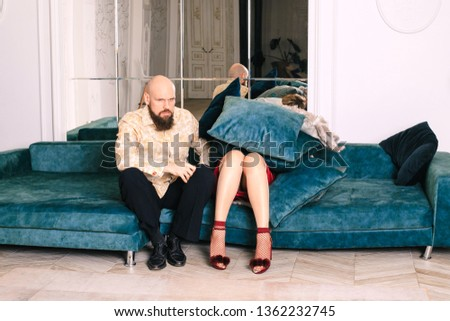 The woman is covered with pillows and things. The woman is lying on the couch on top of a pile of pillows. A man sitting on the couch with a dissatisfied face. Next is a woman littered with things #1362232745
