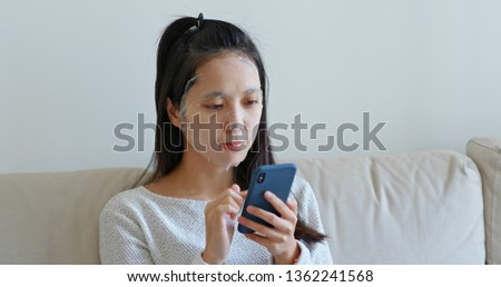 Woman apply paper mask on face at home with use of mobile phone #1362241568