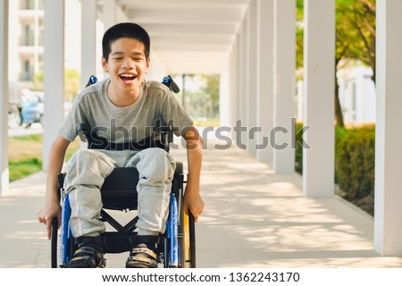 Asian special child on wheelchair is smile happily on ramp for disabled people background and orange light, Life in the education age of disabled children, Happy disabled kid concept. #1362243170