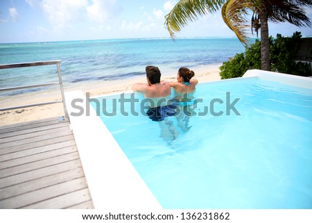 Couple looking at the sea from swimming-pool #136231862