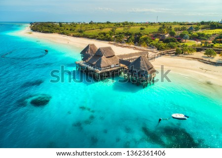 Aerial view of beautiful hotel in Indian ocean at sunset in summer. Zanzibar, Africa. Top view. Landscape with wooden hotel on the sea, azure water, sandy beach, green trees, boat. Luxury resort #1362361406