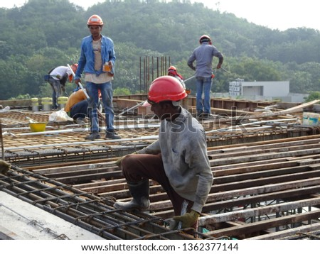 KUALA LUMPUR, MALAYSIA -JULY 16, 2019: Construction workers fabricating steel reinforcement bar inside the timber formwork at the construction site. It was a must process before pouring the concrete.  #1362377144