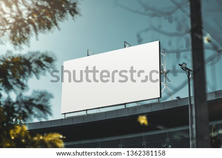 An empty huge poster mockup on the roof of a mall; white template placeholder of an advertising billboard on the rooftop of a modern building framed by trees; blank mock-up of an outdoor info banner #1362381158