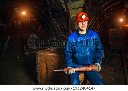 Miner with a jackhammer sitting on a trolley in a coal mine. Work in a coal mine. Portrait of a miner. Copy space. #1362404147