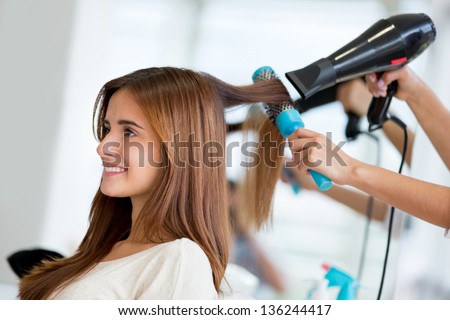 Portrait of a happy woman at the hair salon Royalty-Free Stock Photo #136244417