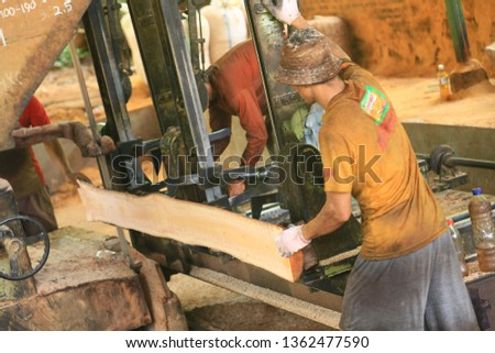 jepara, jawa tengah / indonesia - february 28, 2015: some workers cut teak logs into thin wooden beams with machines at one of the wood processing factories in jepara #1362477590