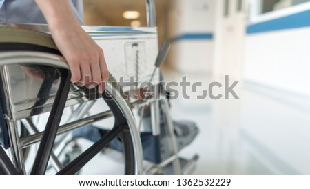 Close up photo of female on wheel chair with orthopedic walking cast. Selective focus at hand with shallow DOF and blurred background with copy space. The wheelchair for disability person. #1362532229