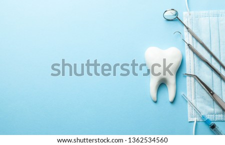 Tooth and dental instruments on blue background. Dental treatment. Dentist tools mirror, hook, tweezers, syringe. Copy space for text #1362534560