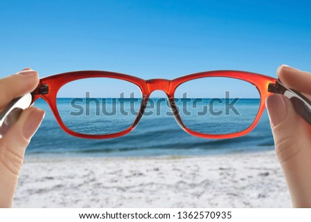 Woman looking through glasses after visiting ophthalmologist, closeup. Improvement of vision #1362570935