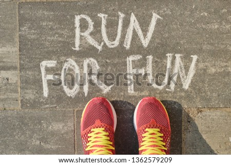 Run for fun, written on gray sidewalk with woman legs in sneakers, top view.