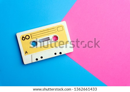 Pop music style attributes eighties, retro old school 80-s or 90-s concept. Audio cassette on a bright blue-pink creative background #1362661433
