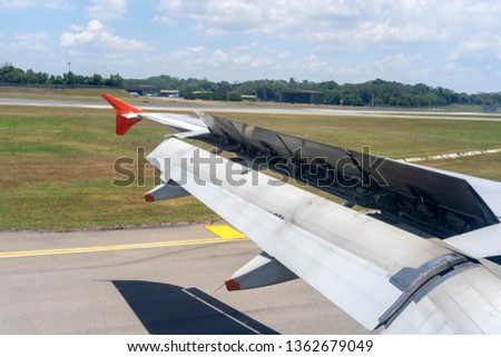 An airplane window view of wing and flaps after landing. Landing aircraft at the airport. Braking of the aircraft on the runway, wing of the plane is in working order. View from window. Close up shot Royalty-Free Stock Photo #1362679049