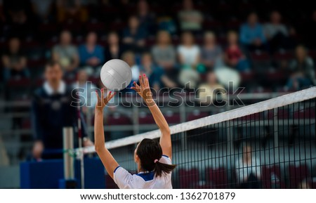 Girl Volleyball player and setter setting the ball for a spiker during a game #1362701879
