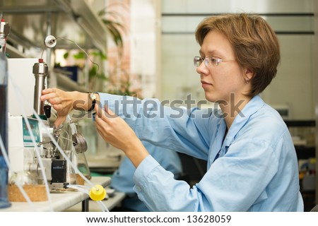 The young nice woman-scientist work with syringe on a background scientific instruments #13628059