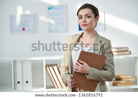 Elegant young businesswoman in formalwear holding clipboard with document while standing in front of camera #1362816791