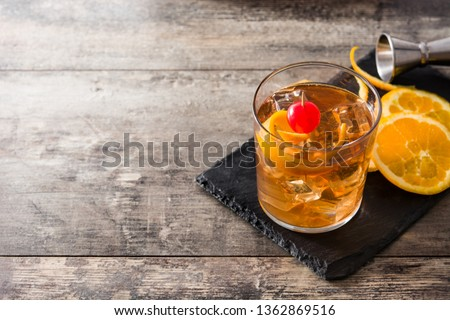Old fashioned cocktail with orange and cherry on wooden table. Copyspace Royalty-Free Stock Photo #1362869516