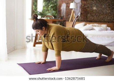 Health, fitness and sports concept. Plus size young brunette woman doing plank exercise on mat in cozy bedroom interior, going to loose extra pounds, become strong and fit, training endurance #1362875681
