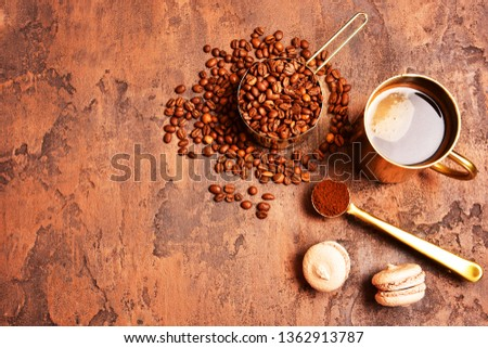 Coffee beans, golden cup of coffee on a brown background. #1362913787
