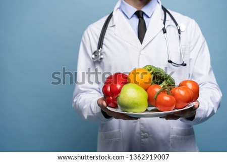 doctor holding plate of fresh vegetables isolated on light blue, healthy eating concept #1362919007