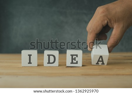 Creative and success concept, hand  putting wood cube block with word idea on wooden table.  #1362925970
