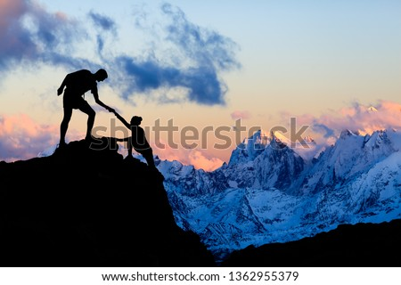 Teamwork couple helping hand, trust in mountains. Team of climbers man and woman hiking, help each other on top of mountain, climbing together, inspiring sunset on Elbrus, Russia. #1362955379