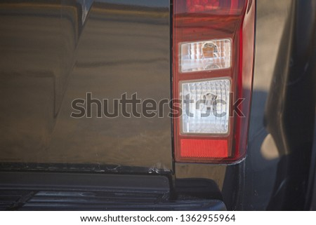 The rear lights of a modern, pickup car in a black color, close-up. #1362955964