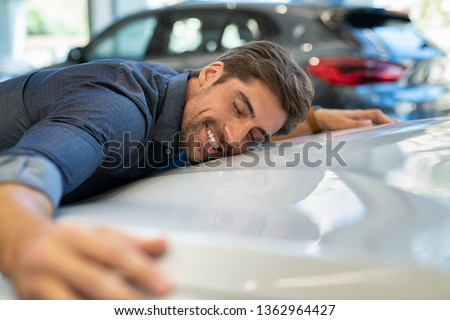 Happy young man hugging his new car in showroom. Satisfied guy with closed eyes embracing the hood of the automobile. Dreaming man lying on car bonnet hugging it. #1362964427