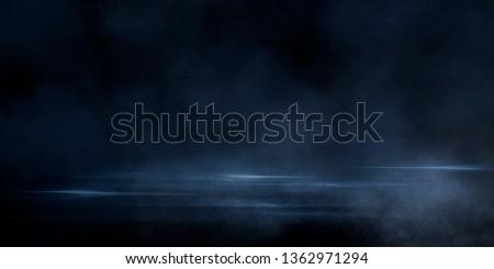 Wet asphalt, reflection of neon lights, a searchlight, smoke. Abstract light in a dark empty street with smoke, smog. Dark background scene of empty street, night view, night city. #1362971294