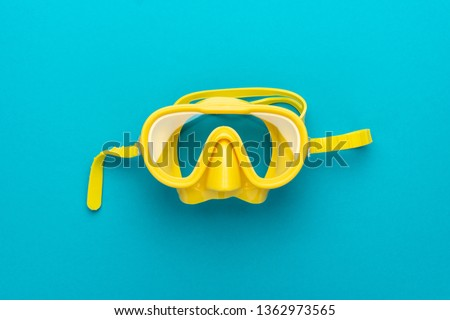 flat lay shot of yellow diving mask over turquoise blue background. minimalist photo of dive mask with central composition #1362973565