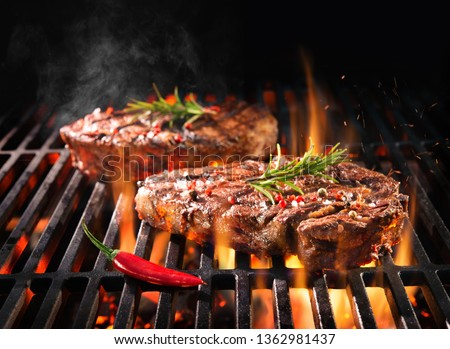 Beef steaks sizzling on the grill with flames #1362981437