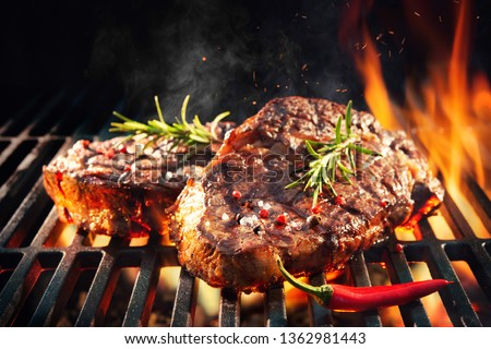 Beef steaks sizzling on the grill with flames #1362981443