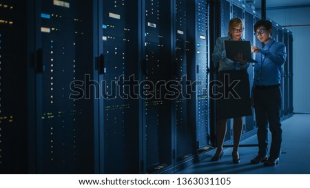 In the Modern Data Center: Engineer and IT Specialist Work with Server Racks, Talking, Doing System Maintenance Check with Laptop Computer. Concept of Diagnostics of the Database, Cybersecurity Check #1363031105