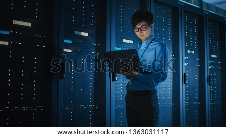 In Dark Data Center: Male IT Specialist Walks along the Row of Operational Server Racks, Uses Laptop for Maintenance. Concept for Cloud Computing, Artificial Intelligence, Supercomputer, Cybersecurity Royalty-Free Stock Photo #1363031117