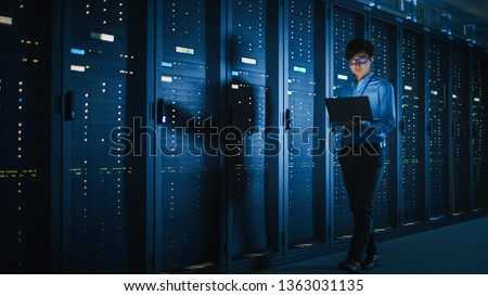 In Dark Data Center: Male IT Specialist Walks along the Row of Operational Server Racks, Uses Laptop for Maintenance. Concept for Cloud Computing, Artificial Intelligence, Supercomputer, Cybersecurity Royalty-Free Stock Photo #1363031135