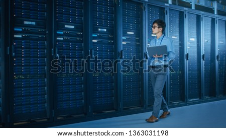 In the Modern Data Center: IT Engineer Working with Server Racks, Uses Laptop for Maintenance and Diagnostics. Checking Stability of the System #1363031198