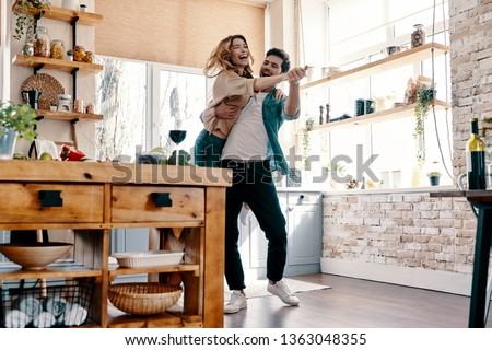 Playful. Full length of beautiful young couple in casual clothing dancing and smiling while standing in the kitchen at home            #1363048355