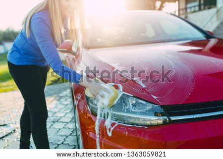 Young woman washing her car with sponge.  #1363059821