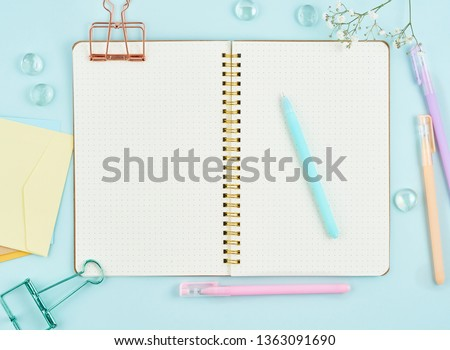 Blank notepad page in bullet journal on blue office desktop. Top view of modern bright table with notebook and flower. Mock up, copy space. Royalty-Free Stock Photo #1363091690