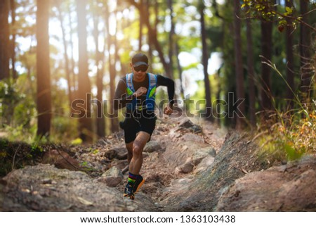 A man Runner of Trail . and athlete's feet wearing sports shoes for trail running in the forest #1363103438