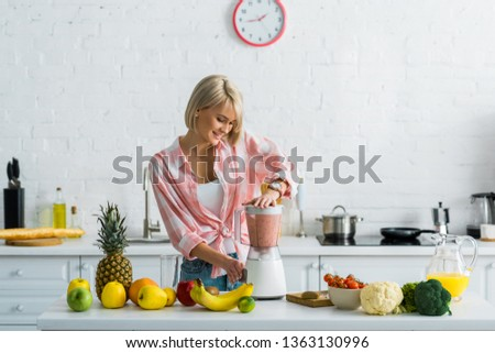 happy young woman preparing tasty nutritious smoothie in blender  #1363130996