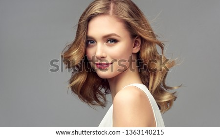 Blonde woman with curly beautiful hair  on gray background. The girl with a pleasant smile. Short haircut . Bob hairstyle #1363140215