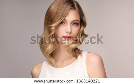 Blonde woman with curly beautiful hair  on gray background. The girl with a pleasant smile. Short haircut . Bob hairstyle  #1363140221