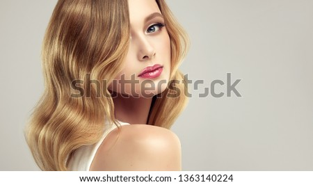 Blonde woman with curly beautiful hair  on gray background. The girl with a pleasant smile. Short haircut . Bob hairstyle  #1363140224