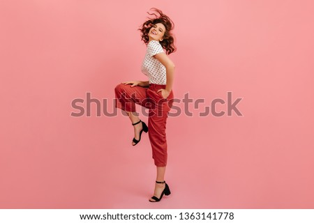 Full length view of joyful woman standing on one leg. Studio shot of wonderful short-haired girl dancing on pink background. #1363141778