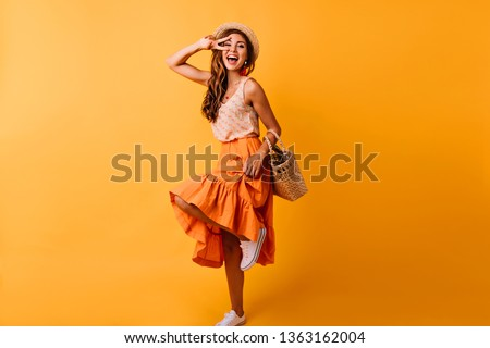 Gorgeous red-haired white woman dancing in studio. Dreamy girl in long skirt having fun on orange background. #1363162004