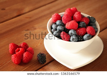 Ripe sweet different berries in white bowl on rustic wooden table. Ripe Red Raspberries closeup. Healthy, organic food and nutrition concept. eating, dieting,  #1363166579
